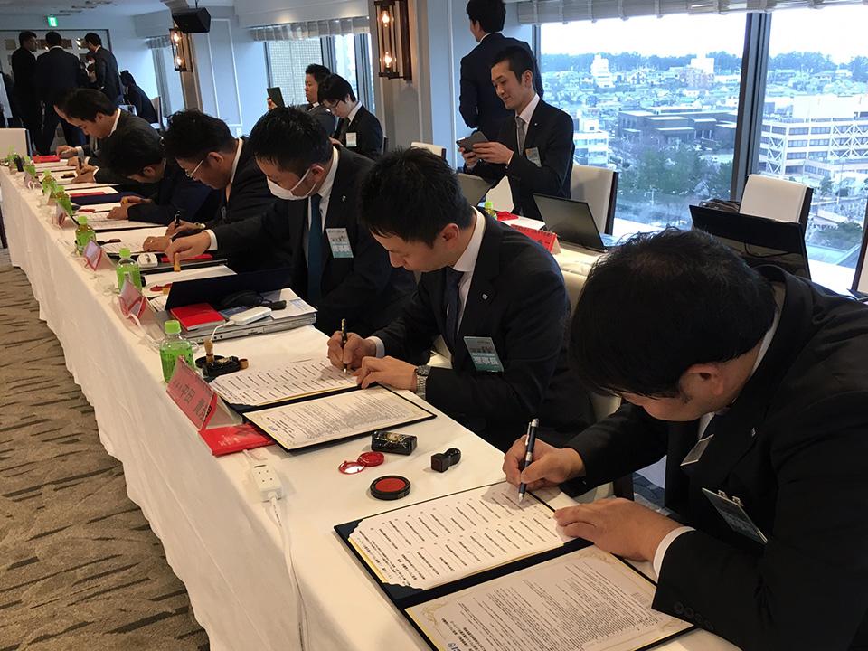 災害時の対応に関する協定書にサインする中田理事長(右から2番目)