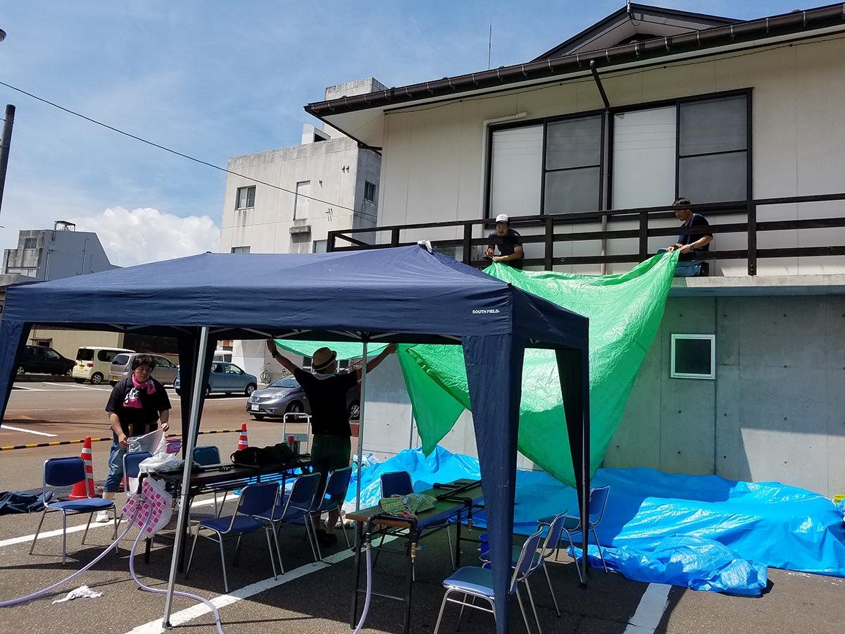 こちらは水風船を作る場所のテント設営風景です。夏の気温で風船が割れたりしないように、細心の注意を払っています。