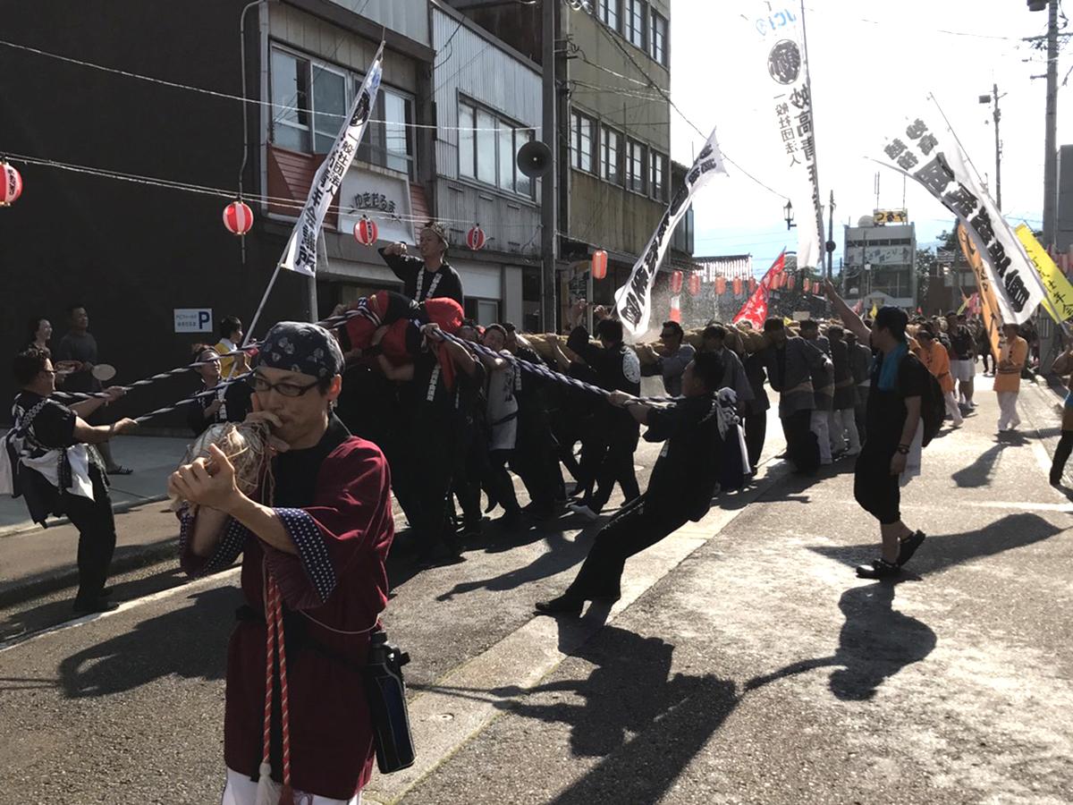 大綱かつぎが始まりました。中田理事長を乗せ、妙高JCの旗も掲げながら、新井の商店街を進んでいきます。