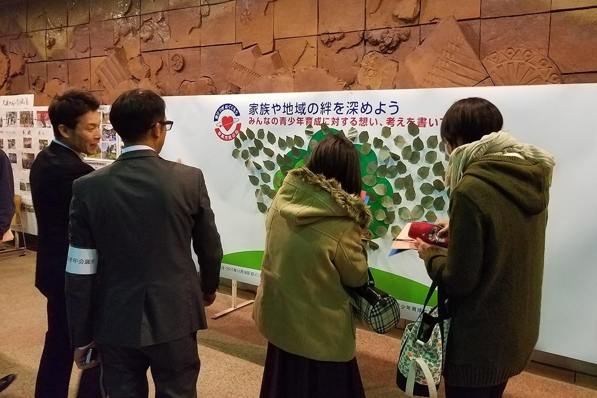 会場のすぐ外では「家族や地域の絆を深めよう」と題して、木のイラストの周りに葉っぱを短冊のように書いて、市民の皆さんが青少年育成に対する思いを書かれていました。
